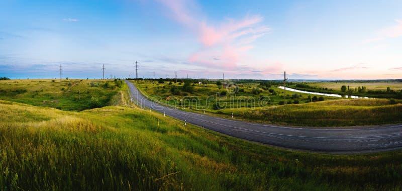 Вымощенная дорога между холмами в заходе солнца стоковое фото rf