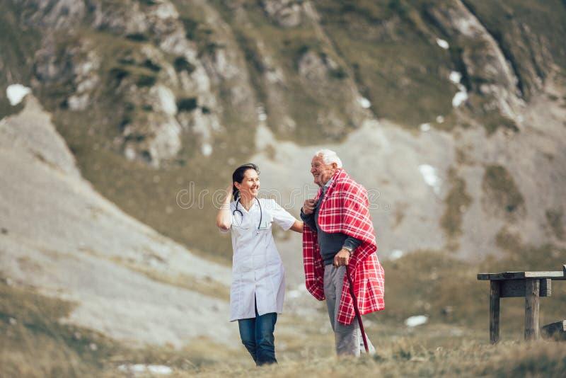 Вынянчите помогая пожилого старшего человека для того чтобы идти на воздух frash стоковая фотография