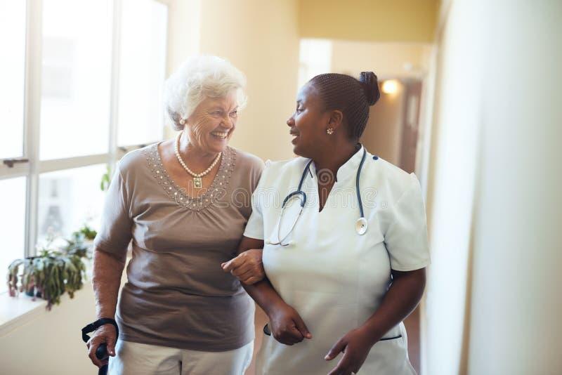 Вынянчите помощь старшей женщины на женщине homeSenior ухода идя в дом престарелых поддержанный попечителем Медсестра помогая sen стоковое изображение rf