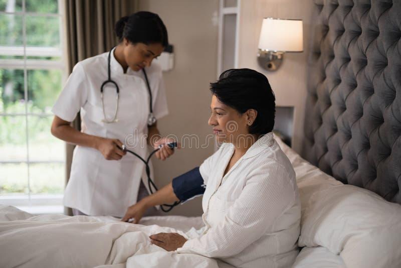 Вынянчите проверять кровяное давление пациента отдыхая на кровати стоковое фото rf