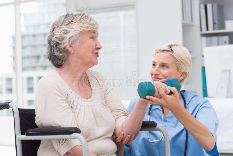 Вынянчите смотреть пациента пока помогающ ей в поднимаясь гантели стоковые изображения rf