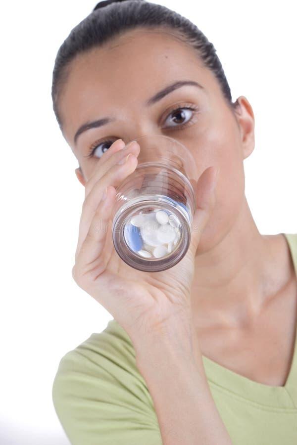 выпивая пилюльки девушки стоковое фото rf