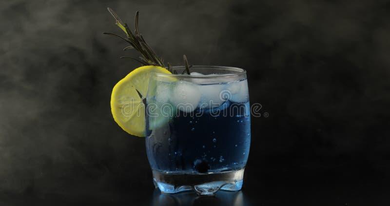 Выпивая стекло с холодным напитком Освежая коктейль лимонада соды голубой стоковые фотографии rf