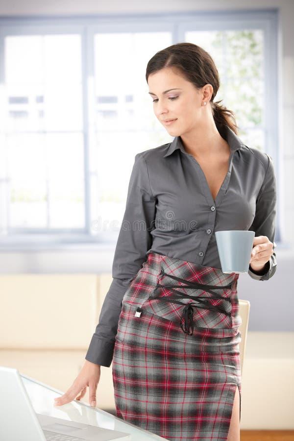 выпивая чай таблицы девушки сексуальный стоящий стоковое фото rf
