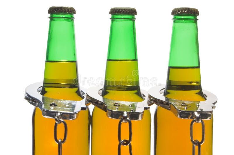 Выпитые пиво и наручники - управляющ принципиальной схемой стоковое фото