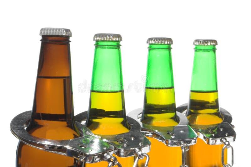 Выпитые пиво и наручники - управляющ принципиальной схемой стоковые фотографии rf