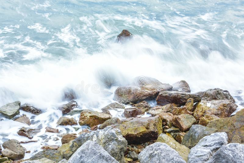 Выплеск волны к скалистому пляжу и белому пузырю стоковое фото rf