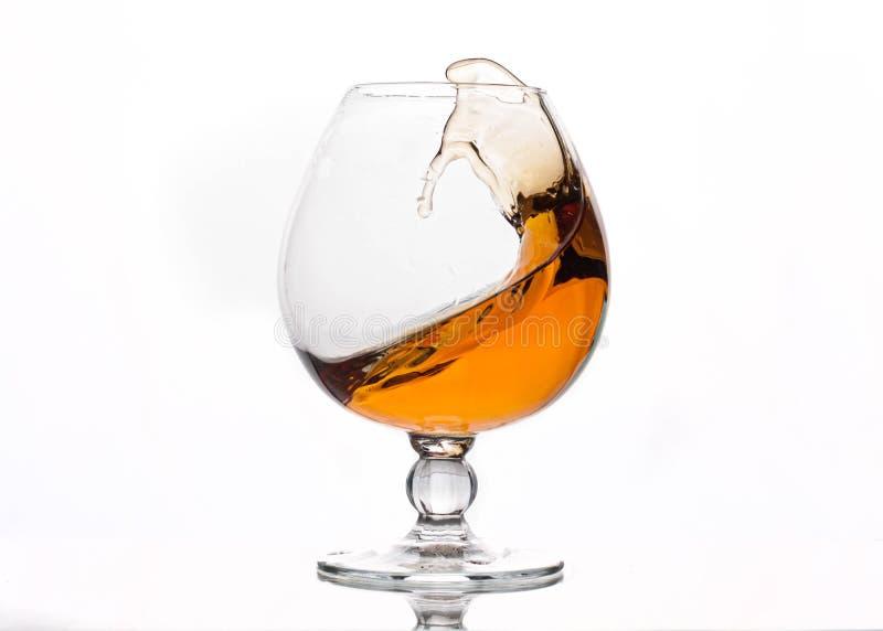 Выплеск коричневого напитка алкоголя в кристаллическом стекле стоковая фотография rf