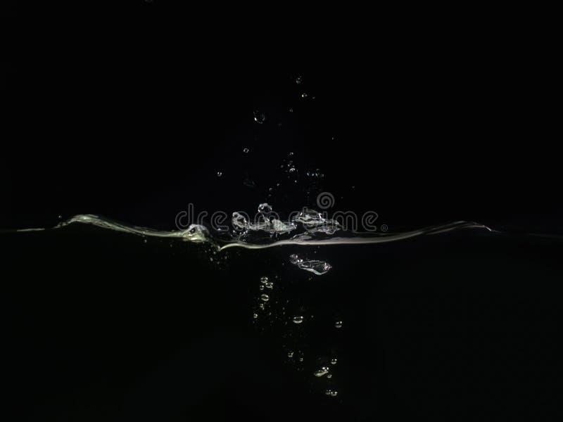 Выплеск на поверхности воды делает волны и пузыри воды изолированные на черной предпосылке, закрывают вверх по взгляду Улучшите д стоковые фотографии rf
