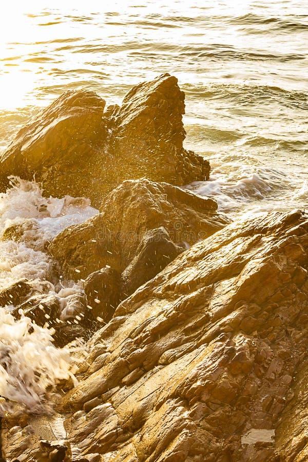 Выплеск океана на острых валунах со светлым отражением стоковое фото rf
