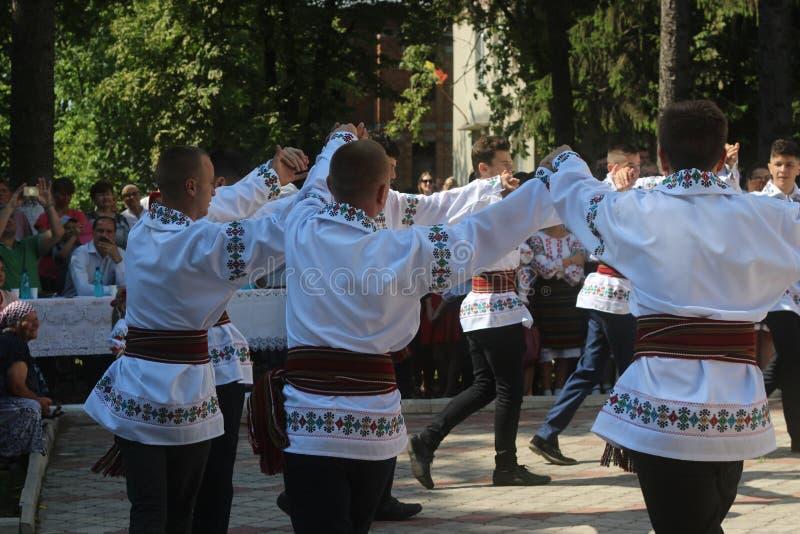Выполнять народные танцы в костюмах молдаванина национальных на фестивале фольклора в деревне Cotala, Молдавия стоковое изображение