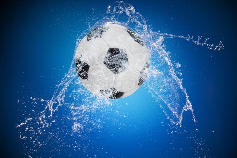Выплеск воды с шариком спорта стоковое фото rf