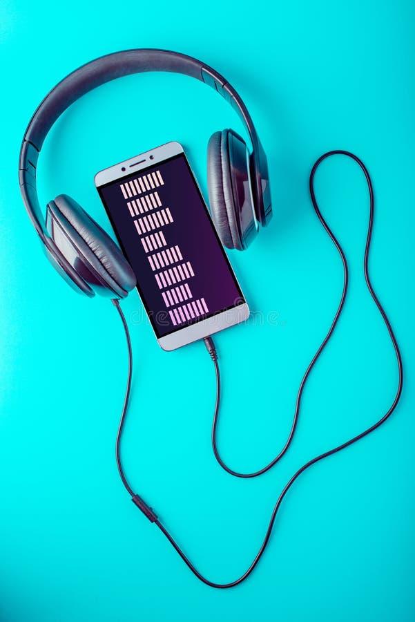Выравниватель на экране телефона при наушники играя музыку на голубой предпосылке стоковые фото