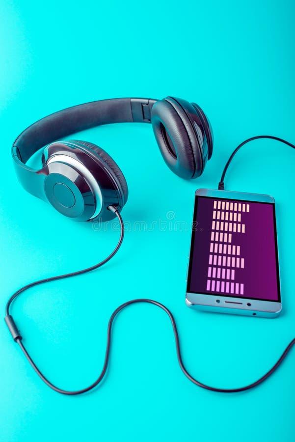 Выравниватель на экране телефона при наушники играя музыку на голубой предпосылке стоковые изображения