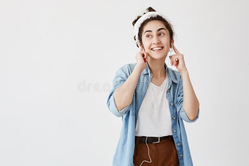 Выразительные счастливые женщина или малолетка с темнотой и вьющиеся волосы в плюшке, слушают к музыке в наушниках, наслаждаются  стоковые изображения rf