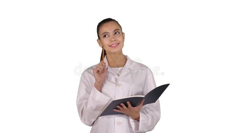 Выразительный молодой женский доктор с творческой тетрадью удерживания идеи и идти на белую предпосылку стоковые изображения rf