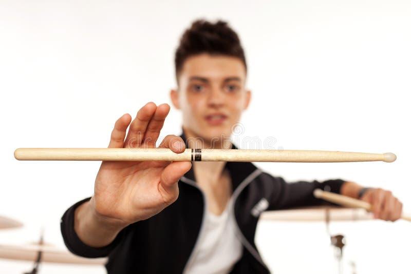 Выразительный молодой барабанщик играя на барабанчиках с ручкой барабанчика стоковое изображение rf