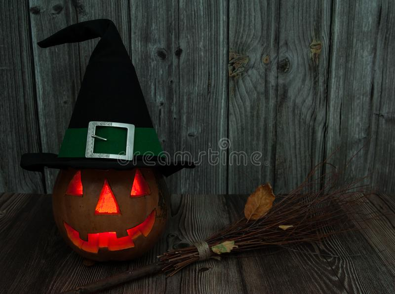 Вырезанный из тыквенного страшного и страшного фонарного шапки в волшебной шляпе со свечой внутри, ведьмская метла на деревянном  стоковые изображения