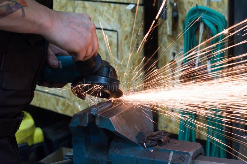 Вырезывание металла точильщиком стоковое фото