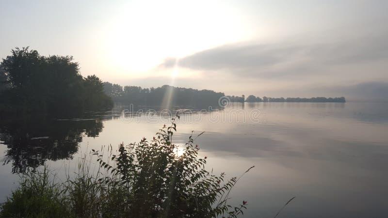 Вырезывание солнечного луча через небо overcast на озере стоковые фотографии rf
