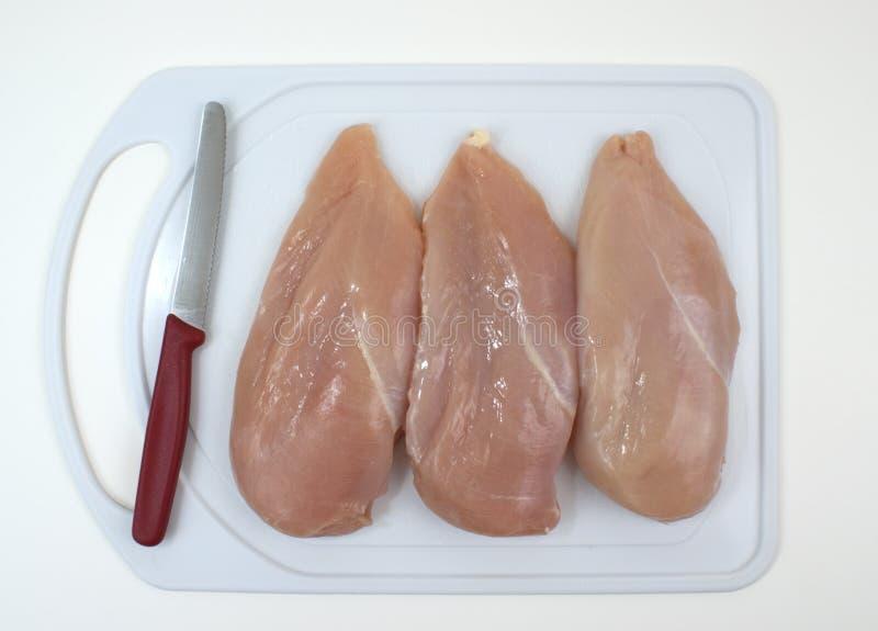 вырезывание цыпленка грудей доски стоковые изображения rf
