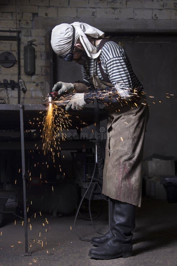 Вырезывание Metalworker на стальной пластине создавая искры, режа утюг стоковые изображения rf