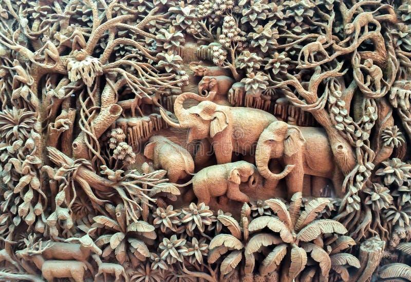 Высекаенная семья слона в древесине на деревянной рамке стоковые изображения rf