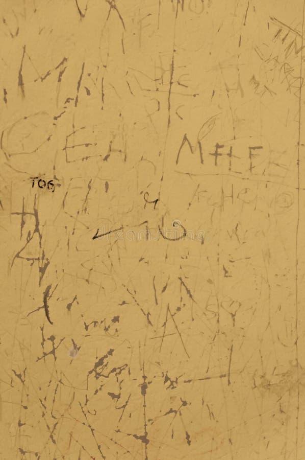 Выскобленная желтая поверхность поцарапанного стенда школы с высекаенными надписями, метками scribble и писать от студентов как стоковое изображение