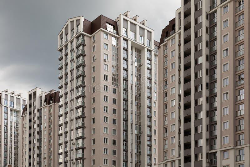 Высокая плотность людей, путешествующих по современному высококлассному жилому зданию на фоне облачного неба, диагональный вид стоковая фотография