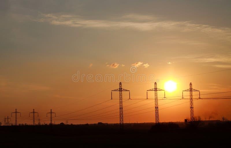 Высокие башни линии электропередач электричества на драматическом заходе солнца стоковое фото rf