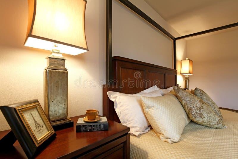Высокие столбы кладут в постель с красивыми бежевыми постельными принадлежностями и nightstand. Cl стоковые изображения