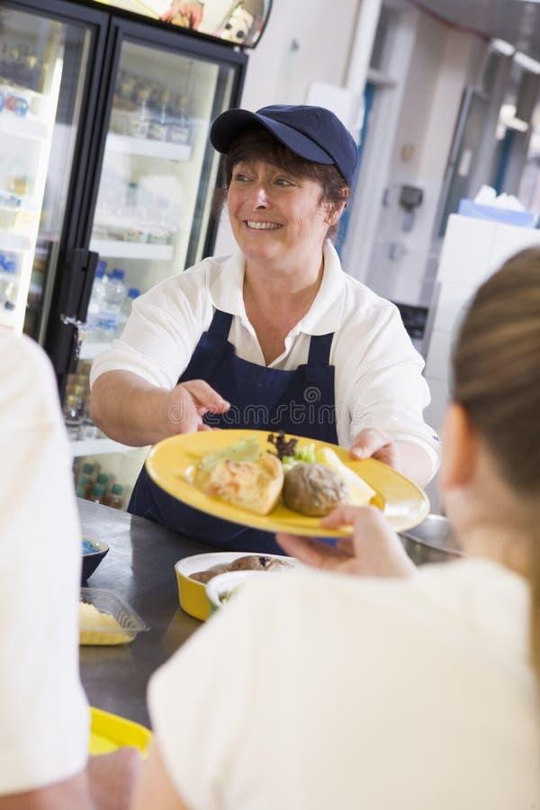 высокие студенты сервировки школы обеда к женщине стоковое фото