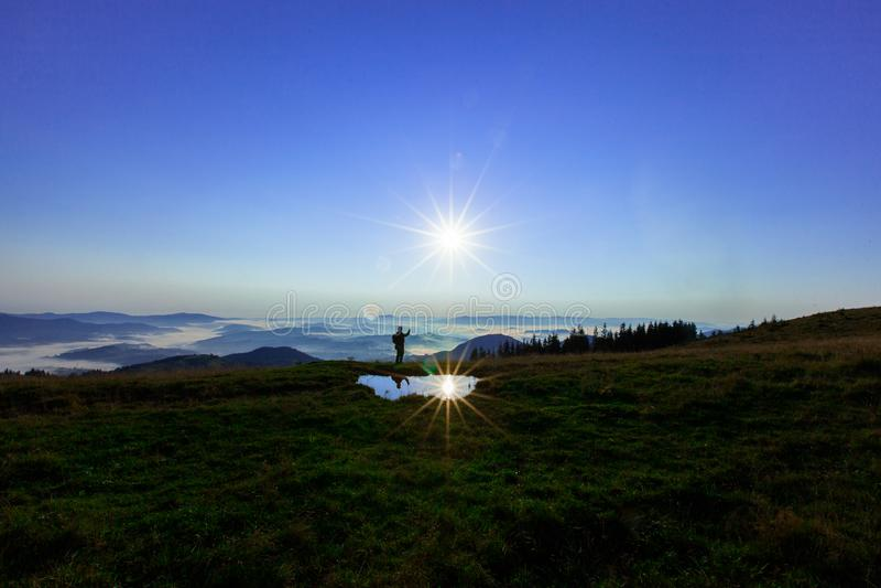 Высокий в горах над облаками молодой человек ищет клетчатое соединение держа его телефон высоко стоковые изображения rf