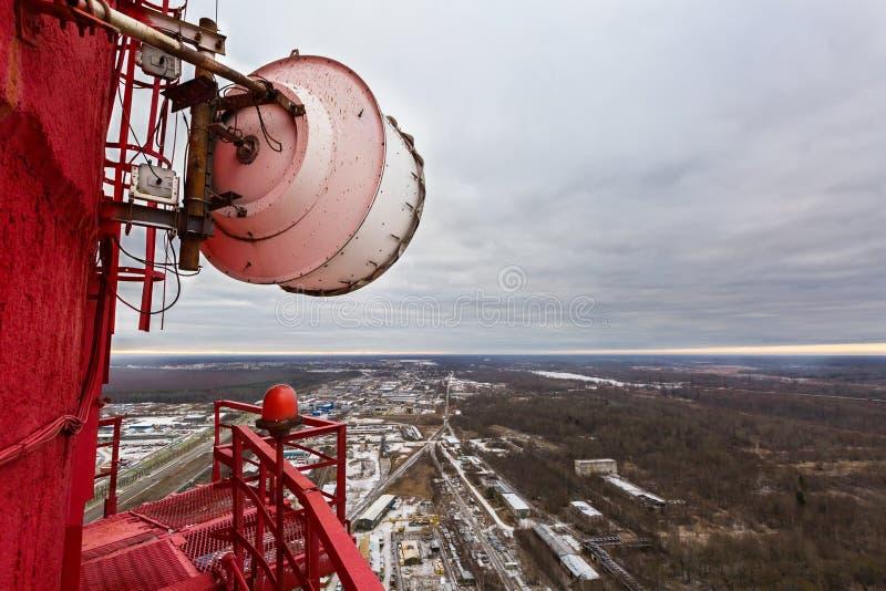 Высокий красный камин электростанции с на открытом воздухе шестерней микроволны большой емкости радиосвязи и огромной антенной ра стоковые изображения rf