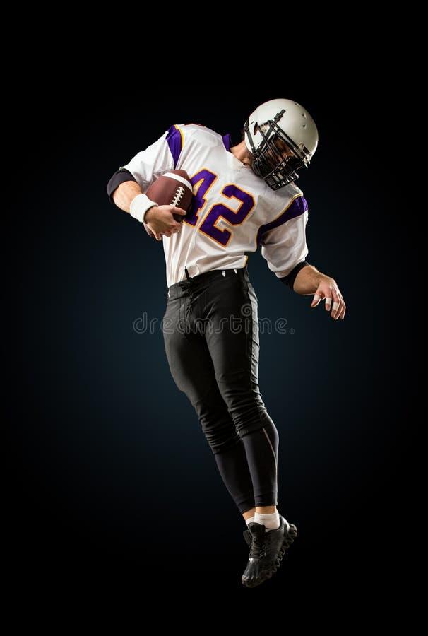Американский футболист в действии Высокий прыжок американского футболиста стоковое изображение