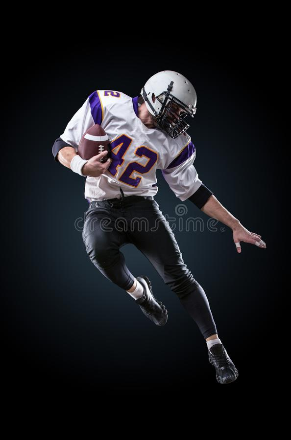 Американский футболист в действии Высокий прыжок американского футболиста стоковое фото