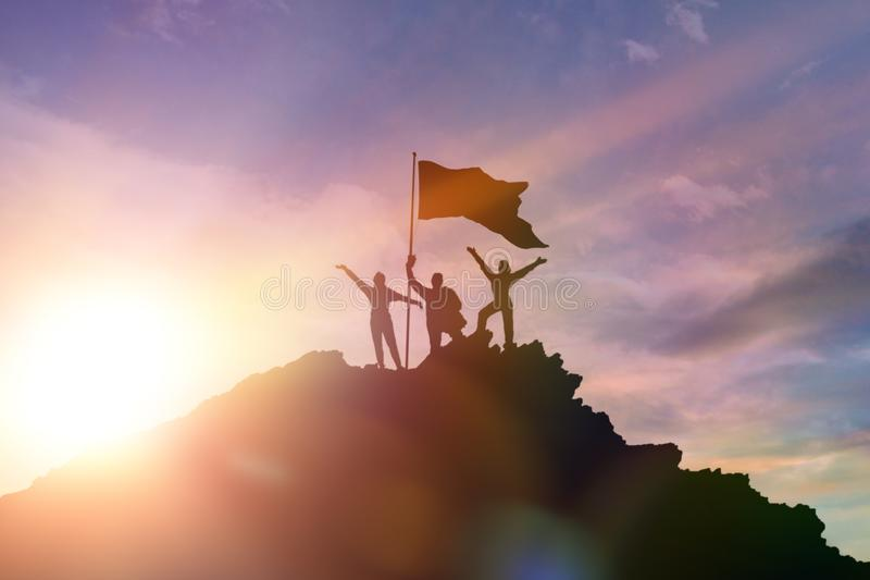 Высокий achiever, силуэты 3 людей держа na górze горы для того чтобы поднять их руки вверх стоковые фото
