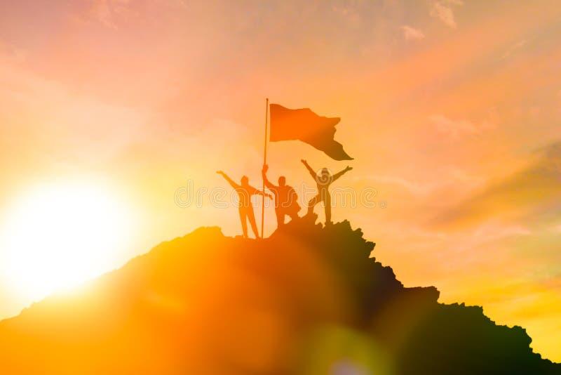 Высокий achiever, силуэты 3 людей держа na górze горы для того чтобы поднять их руки вверх стоковая фотография