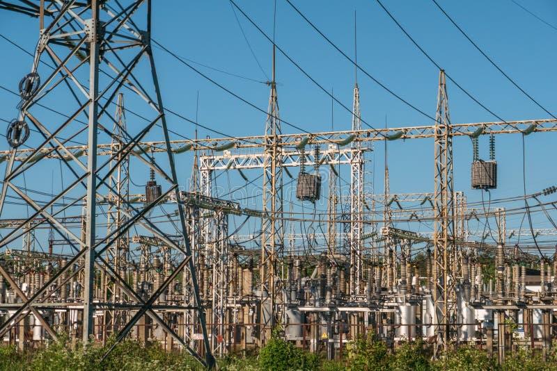 Высоковольтная электростанция с высокорослыми башнями и проводами, промышленной предпосылкой электричества стоковые фото