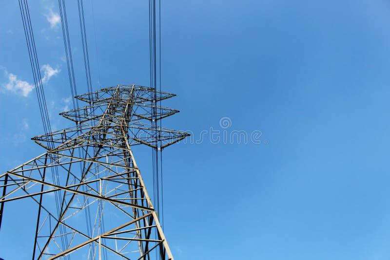 Высоковольтные башня или линия передачи электроэнергии с голубым небом и белым облаком стоковые изображения rf