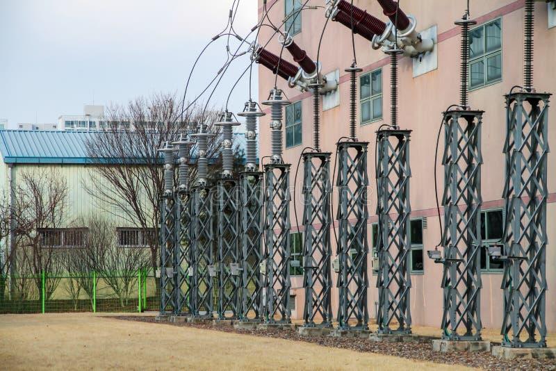Высоковольтные поляки установлены рядом со зданием стоковое фото rf