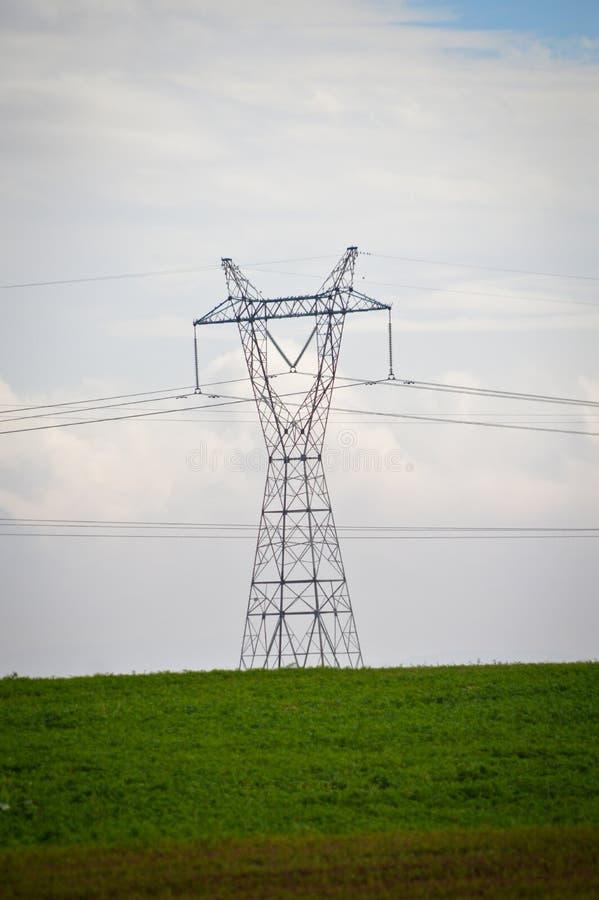 Высоковольтные электрические штендер, трава и небо стоковое изображение