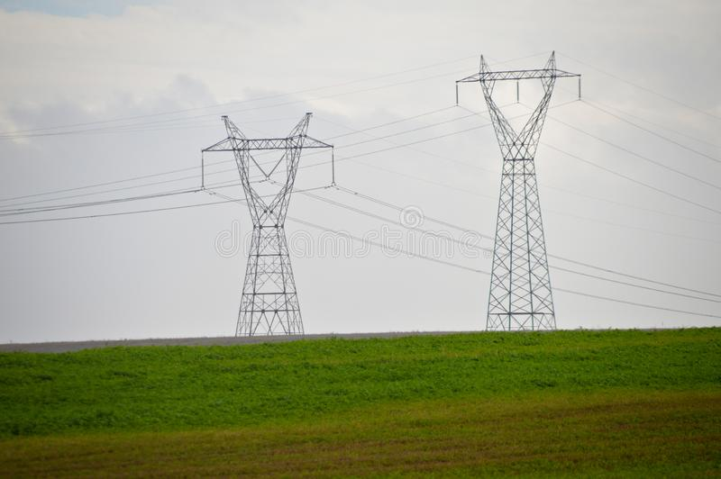 Высоковольтные электрические штендер, трава и небо стоковая фотография rf