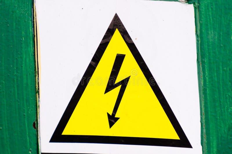 Высоковольтный знак внимания, не касается Черная молния на желтой предпосылке в треугольнике стоковое изображение