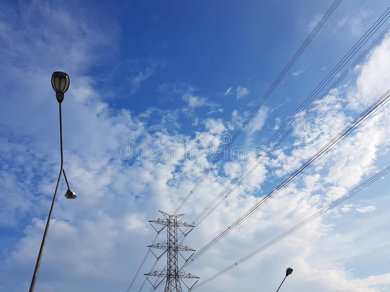Высоковольтная башня в пасмурной предпосылке голубого неба с lig улицы стоковые фотографии rf