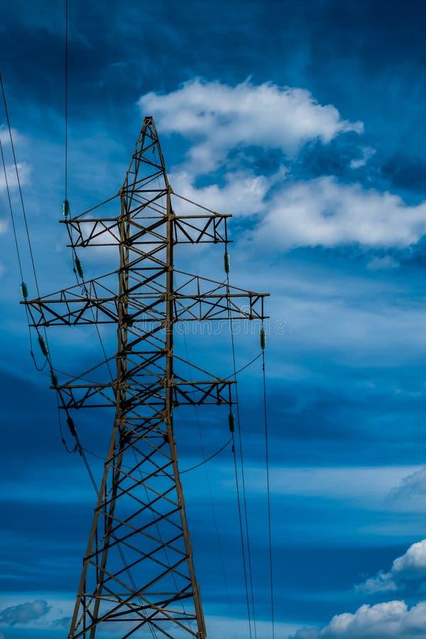 Высоковольтная башня линии электропередач с голубым небом на backgound стоковое фото
