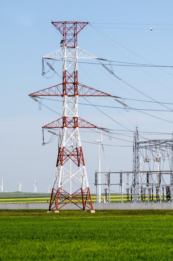 Высоковольтные башня и ветрянки стоковая фотография rf