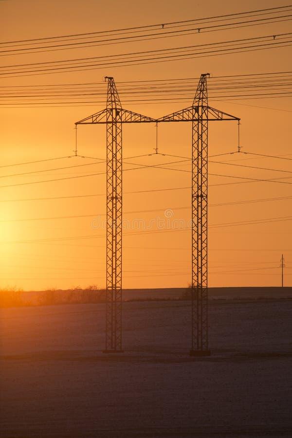 Высоковольтные линии и опоры силы в ландшафте зимы аграрном на заходе солнца стоковые фото