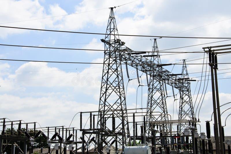 Высоковольтные линии электропередач с опорами электричества на голубом небе стоковые фото
