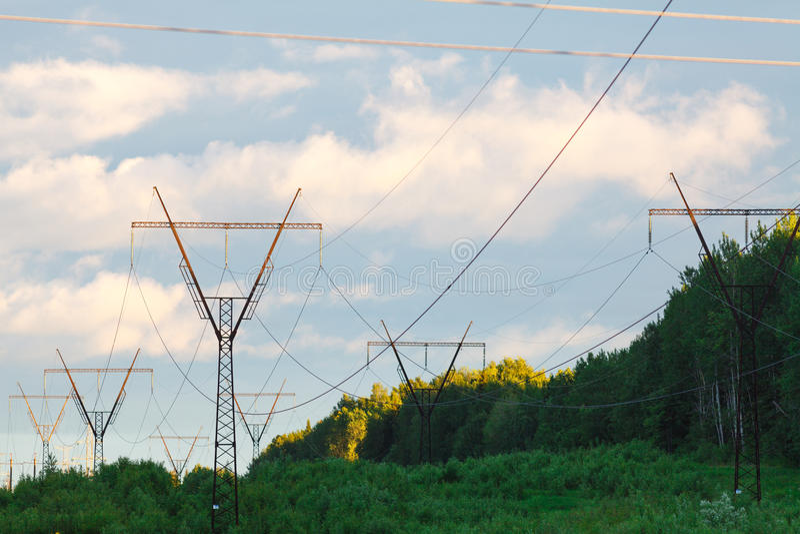 Высоковольтные опоры силы против лучей голубого неба и солнца стоковая фотография rf